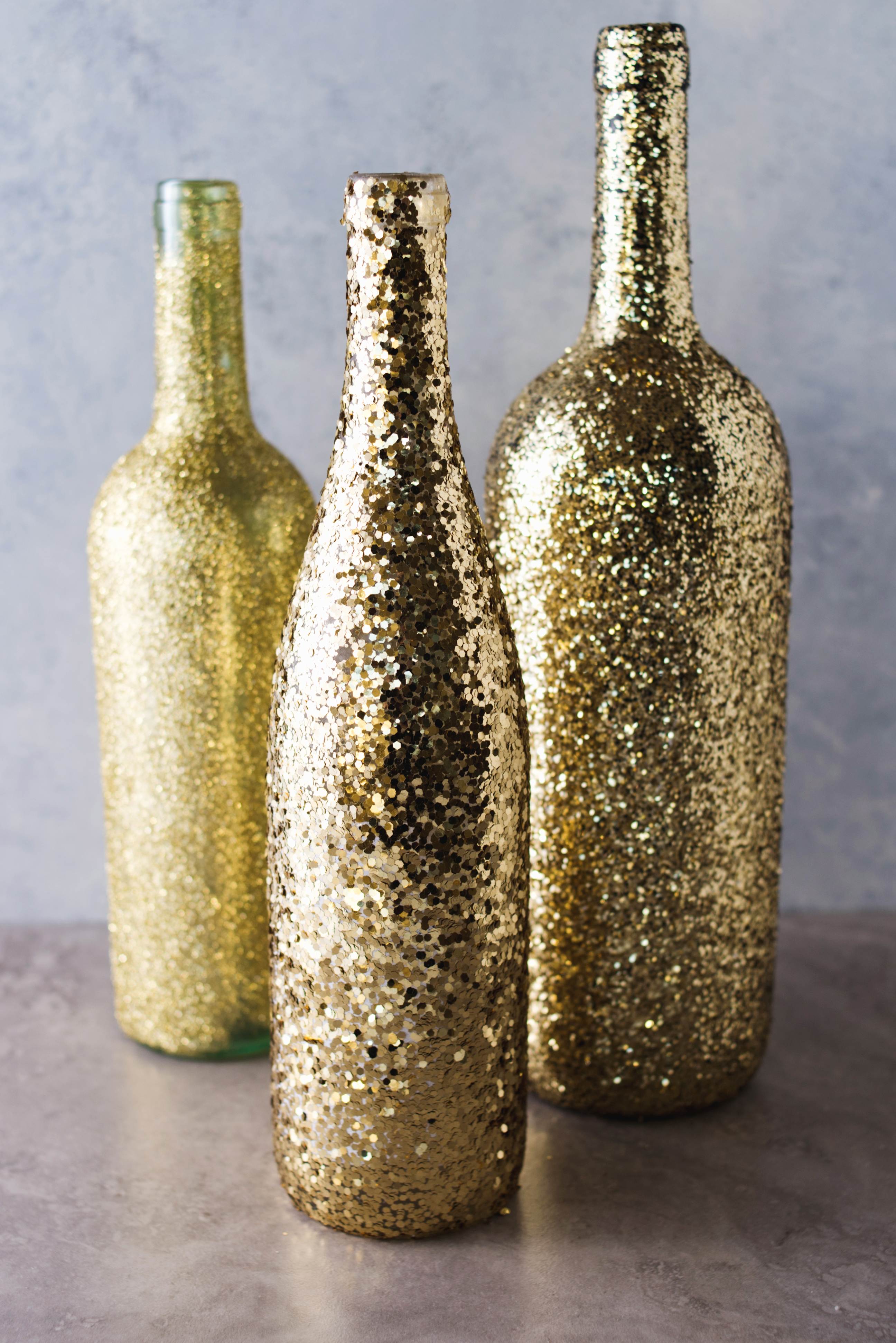 Diy wine bottle glitter vases a little craft in your day supplies three assorted sized wine bottles assorted gold glitter decou page paintbrush floridaeventfo Gallery